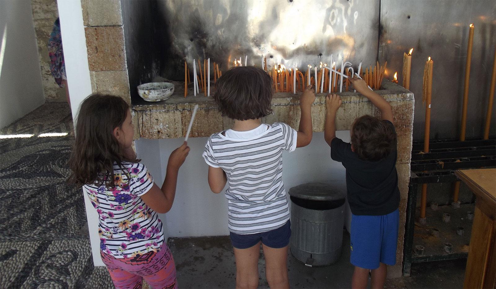 tre bambini che accendono ceri votivi davanti ad un'icona